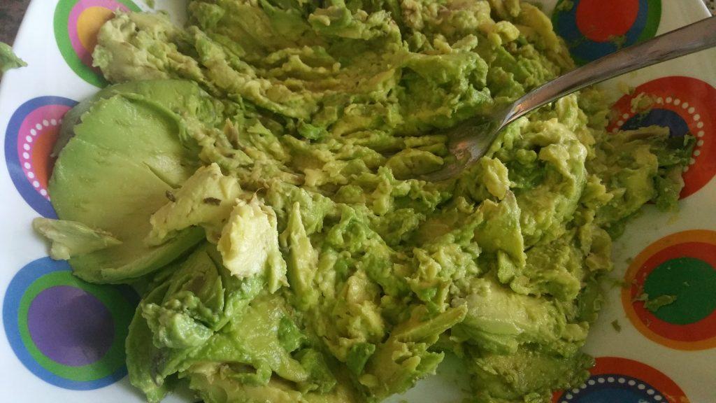 Smashing avocados with fork